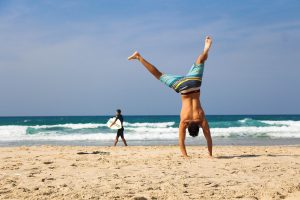 Image of an athletic man doing a handstand on a beach with man in the distance with a surfboard